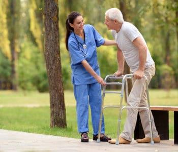 female nurse helps an elderly man to walk