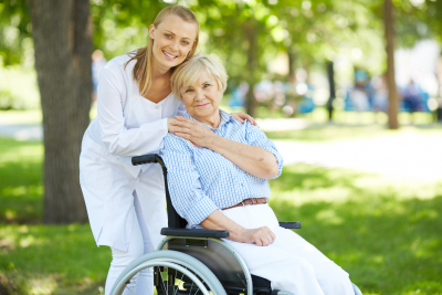 nurse and elder woman in a wheelchair smiling at the camera