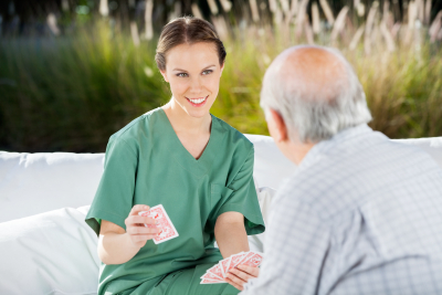 caregiver playing cards with senior man